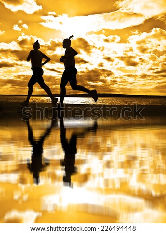 silhouette of two women running at sunrise  at sunny beach Girls run by beach ocean at sunset along horizon against sun shine Phases of motion Reflection on water - stock photo