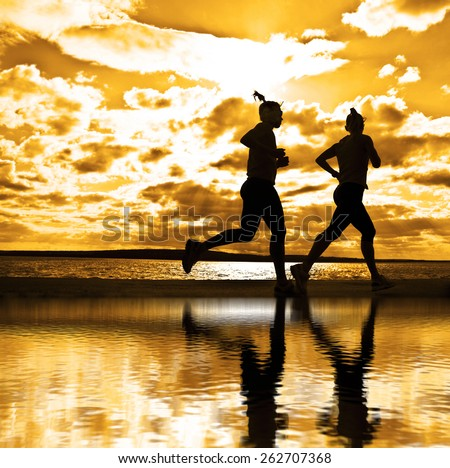 silhouette of two women running at sunset or sunrise Girl move along sun set sunny beach Reflection light on water texture  Couple Doing sports exercises against sky with clouds - stock photo