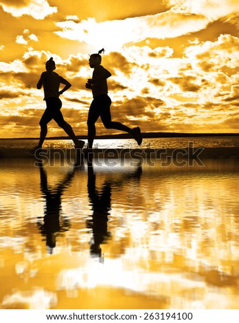 silhouette of two women running at sunset or sunrise Girl move along sun set sunny beach Reflection light on water texture lesbian Couple Doing sports exercises against sky with clouds - stock photo