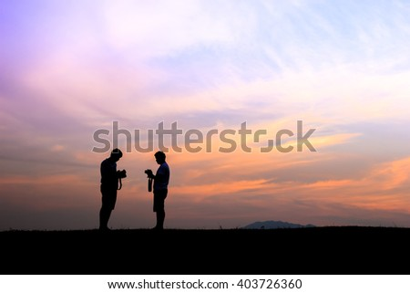 Silhouette of two young photographers during the sunset.