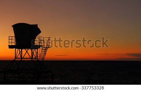 Silhouette of Typical Lifeguard tower station in California at sunset - stock photo