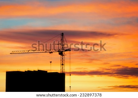 Silhouette of unfinished building and crane tower during sunrise - stock photo