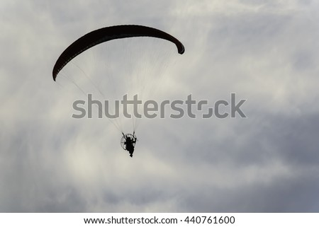 Silhouette of unidentifiable powered paraglider at sunset, for themes of adventure, lifestyle, recreation (shallow depth of field) - stock photo