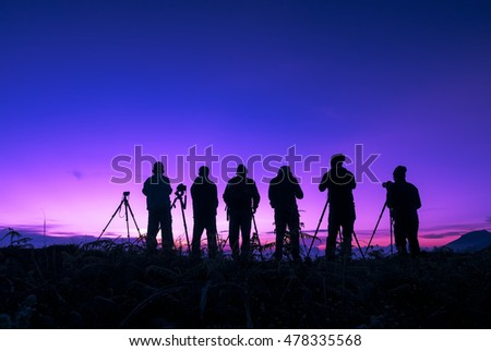 Silhouette of unidentified photographers shooting sunrise on a mountain.