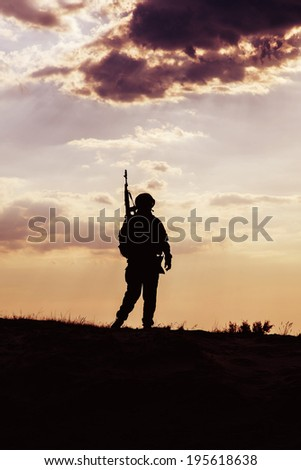 Silhouette of US soldier with rifle  against the sunset - stock photo