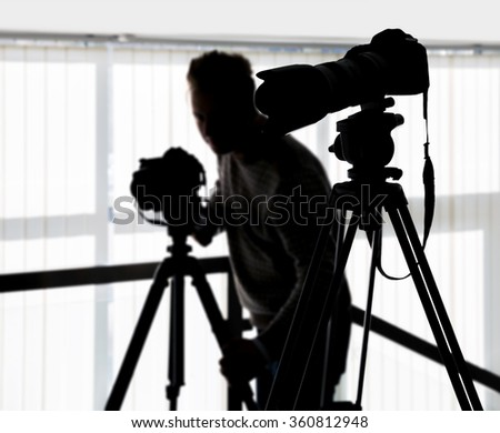 Silhouette of video and photographic equipment on a tripod at the workplace indoors. Photographer in the background