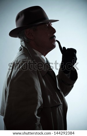 Silhouette of vintage detective with mustache and hat. Smoking pipe. Studio shot. - stock photo