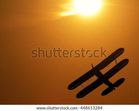 Silhouette of vintage single engine propeller biplane aircraft banking left while climbing towards scenic sunset detail close up view - stock photo