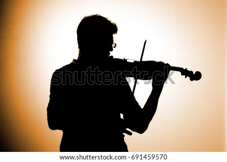 Silhouette of violin player on bright background similar to sunset