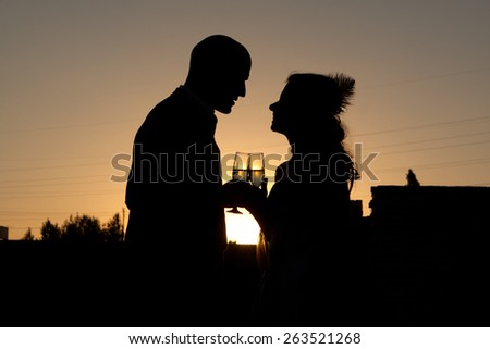 Silhouette of wedding couple at sunset - stock photo