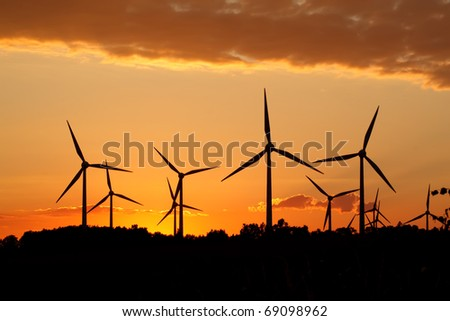 Silhouette of wind power station on sunset - stock photo
