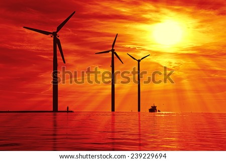 Silhouette of wind power stations over the sea at sunset. - stock photo