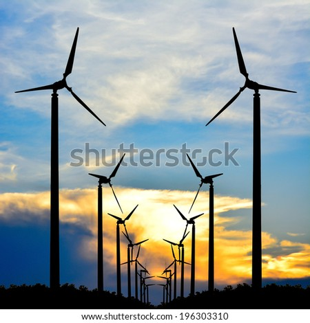 Silhouette of wind turbine at sunset  - stock photo