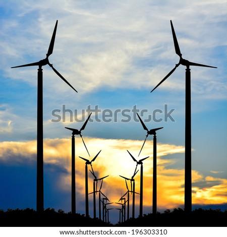 Silhouette of wind turbine at sunset  - stock photo