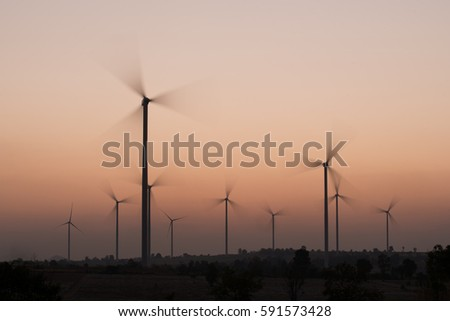 silhouette of wind turbines spinning at sunset