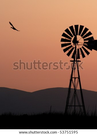 Silhouette of windmill, bird, and California hills. - stock photo