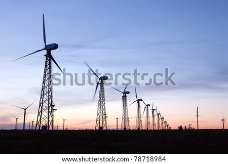 silhouette of windmill electric power turbines at sunset