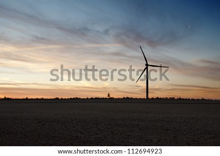 Silhouette of windmill generator at dusk