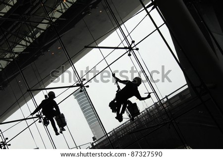 Silhouette of Window Cleaners, known as window washers workers working by hanging from the ceiling, backlit scene