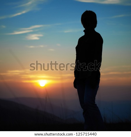Silhouette of woman against sunset with orange clouds and sky - stock photo