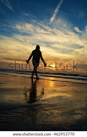 Silhouette of woman and dog at beach during beautiful sunset