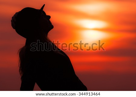 Silhouette of woman at sunset with hat with red sky