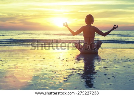 Silhouette of woman at yoga pose on the beach during an amazing sunset. - stock photo