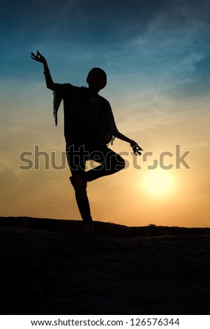 Silhouette of woman balancing on one foot and making a hand gesture. Setting sun on background.