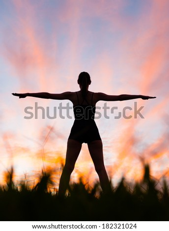 Silhouette of woman doing yoga. - stock photo