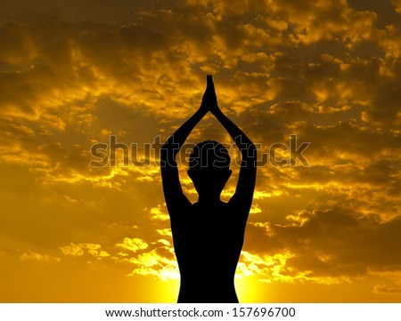 Silhouette of woman doing yoga meditation during sunset with natural golden sunlight outdoor. - stock photo