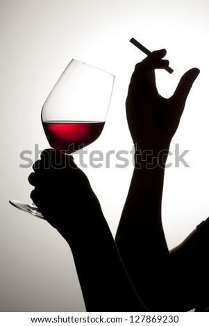 silhouette of woman drinking wine with cigarette - stock photo