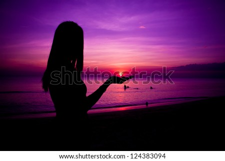 Silhouette of woman during colorful sunset - stock photo