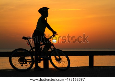 silhouette of woman enjoy sunrise on the beach in the morning