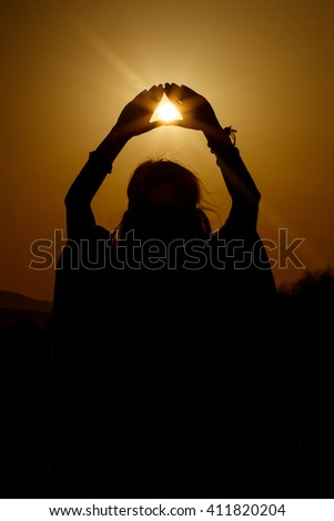 silhouette of woman hands holding sun in triangle on background of beautiful sunset - stock photo