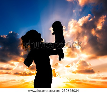 silhouette of woman holding a baby at sunset