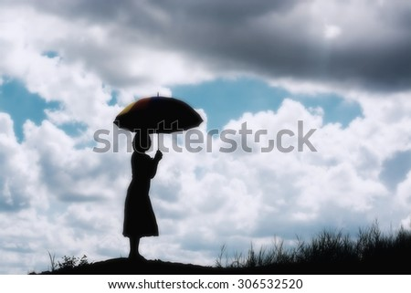 silhouette of woman holding umbrella sunny day