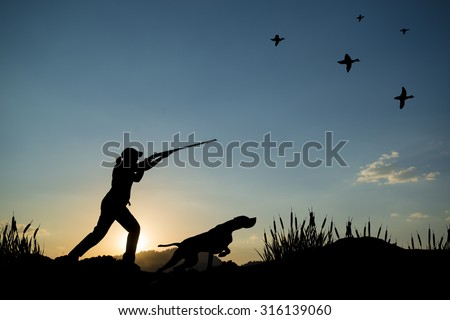 Silhouette of woman hunter at sunset. Duck hunting with dogs. - stock photo