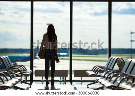 Silhouette of woman in an airport lounge waiting for flight aircraft - stock photo