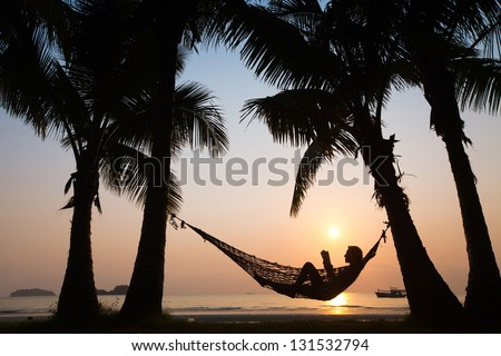 silhouette of woman in hammock at sunset on the beach - stock photo