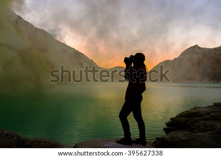 Silhouette of woman is taking photo at  crater lake of volcano before sunrise. - stock photo