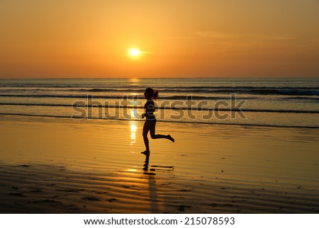 Silhouette of woman jogger running on sunset beach, fitness and healthy life concept