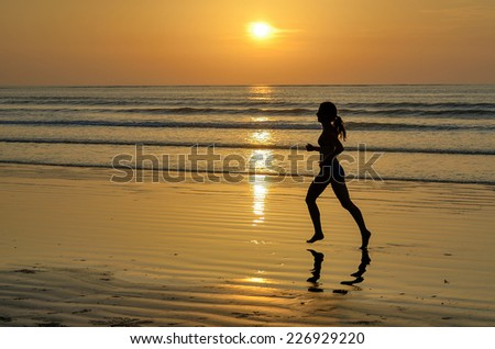 Silhouette of woman jogger running on sunset beach, fitness and healthy life concept  - stock photo
