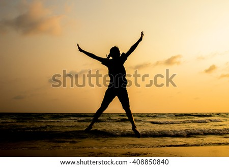 Silhouette of woman jumping and happy on the beach