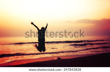 silhouette of woman jumping and wave on the beach with sunrise in the sea, blurred
