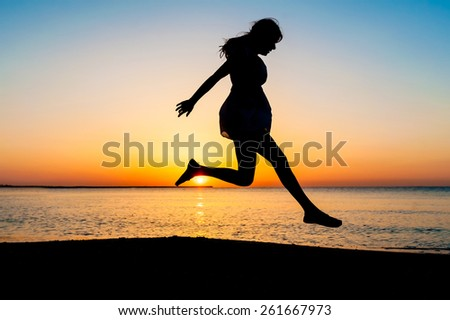 Silhouette of woman jumping in the air on the beach at sunrise.