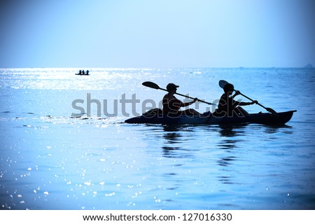 Silhouette of woman kayaking - stock photo