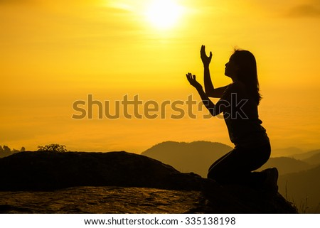 Silhouette of woman kneeling and praying over beautiful sunrise background - stock photo