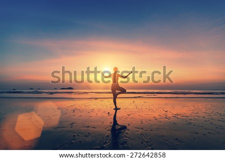 Silhouette of woman meditating on the sea beach. Yoga and fitness. - stock photo