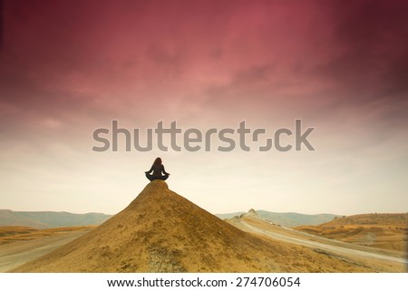 Silhouette of woman meditating on top of a hill