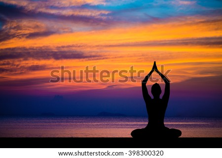 Silhouette of woman on the background of the stunning sea and sunset making yoga exercises, asanas.